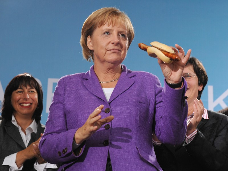 ERFURT, GERMANY - SEPTEMBER 15:  German Chancellor Angela Merkel holds a original grilled  Thuringian sausage during an election rally on September 15, 2009 in Erfurt, Germany. German Chancellor Angela Merkel of the Christian Democratic Union (CDU) tours during her election campaign rally through six German cities in the historic 'Rheingold' train. The 17th German federal election is scheduled for September 27, 2009 and will be held to elect the members of the Bundestag, the federal parliament of Germany.  (Photo by Andreas Rentz/Getty Images)