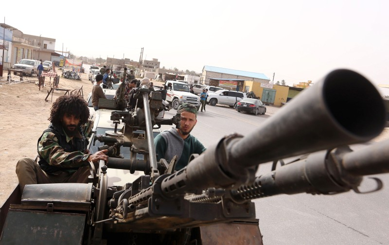 TOPSHOT - Members of a brigade loyal to the Fajr Libya (Libya Dawn), an alliance of Islamist-backed fighters, drive pick up trucks mounted with machine guns during a military parade following battles against the Islamic State (IS) group, in the city of Sabratha, west of the capital Tripoli, on February  28, 2016. On February 19, a US air strike near Sabratha targeted a suspected IS training camp, killing 50 people. / AFP / MAHMUD TURKIA        (Photo credit should read MAHMUD TURKIA/AFP/Getty Images)