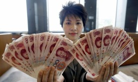 HONG KONG, CHINA:  A Bank of China teller shows 100 renminbi (yuan) notes at its headquarters in Hong Kong, 25 February 2004.  The Bank of China (BOC) along with other local banks started offering to its customers transact business in yuan currency, a move seen as a step forward to consolidating two economies namely Hong Kong and the mainland.     AFP PHOTO/TED ALJIBE  (Photo credit should read TED ALJIBE/AFP/Getty Images)