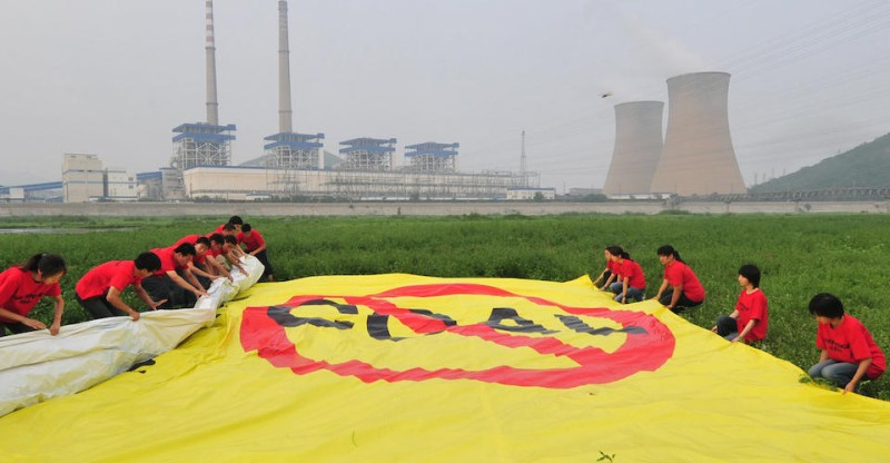 Greenpeace activists unfurl a banner condemning the use of coal, on a dry riverbed near one of the Beijing's biggest coal-fired power plants on July 28, 2009. China's powerful energy companies must play a greater role in fighting climate change and building the nation a low-carbon sustainable energy sector, top environmental group Greenpeace China said in a report on the coal use of China's top ten power companies. According to the report, in 2008, China's biggest three power companies emitted more greenhouse gasses than the UK. AFP PHOTO/Frederic J. BROWN (Photo credit should read FREDERIC J. BROWN/AFP/Getty Images)