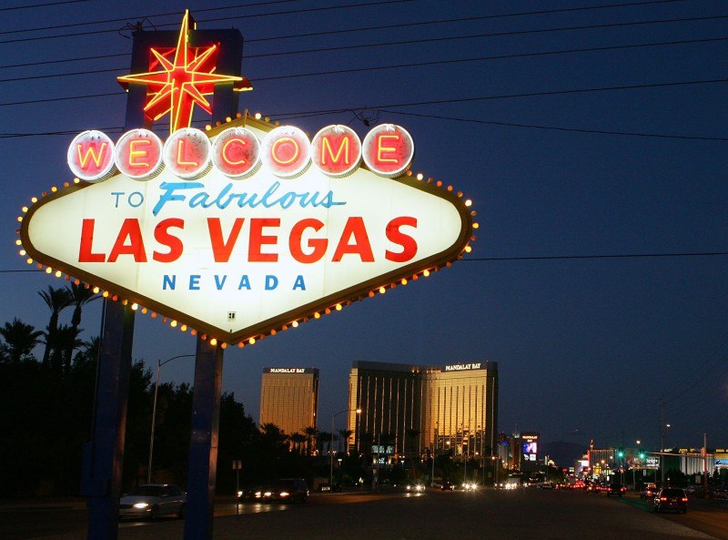 LAS VEGAS - NOVEMBER 11:  Traffic passes by the famous sign welcoming motorists on the south end of the Las Vegas Strip November 11, 2005 in Las Vegas, Nevada. The Mandalay Bay Resort & Casino is in the background.  (Photo by Ethan Miller/Getty Images)