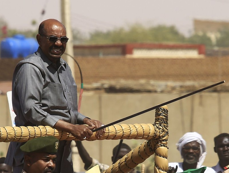 Sudan's President Omar al-Bashir stands on a pick-up truck during a campaign rally for the upcoming presidential elections in El-Fasher, in North Darfur, on April 8, 2015. Sudanese go to the polls on April 13 in legislative and presidential elections widely expected to return Omar al-Bashir to power for another five years. AFP PHOTO / ASHRAF SHAZLY        (Photo credit should read ASHRAF SHAZLY/AFP/Getty Images)