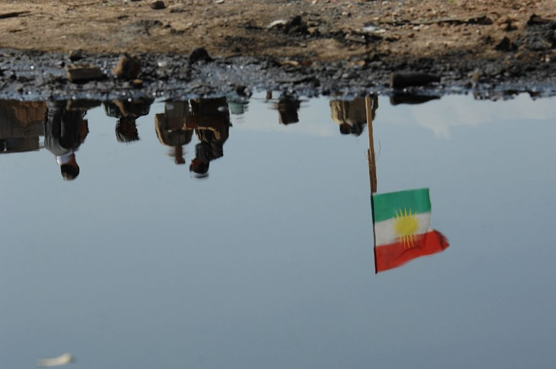 KIRKUK, IRAQ - MARCH 13: A Kurdish flag at apeshmerga checkpoint is reflected in pools of oil with damaged oil pipeline infrastructure, as Iraqi Kurdish forces push the frontline forward against ISIS forces in the Tal al-Ward district 20 miles southwest of Kirkuk, Iraq, on March 13, 2015. These peshmerga units of the Patriotic Union of Kurdistan (PUK) faction have made significant gains against villages held by ISIS, in concert with an Iraqi government and Shiite militia attack further south to free Tikrit from ISIS control, with a joint aim of squeezing the jihadist militants from Iraq. Since ISIS swept from Syria in June, 2014, Kurdish forces in northern Iraq have expanded their control over oil-rich territories disputed with Baghdad such as Kirkuk and its oil and gas facilities. (Photo by Scott Peterson/Getty Images)