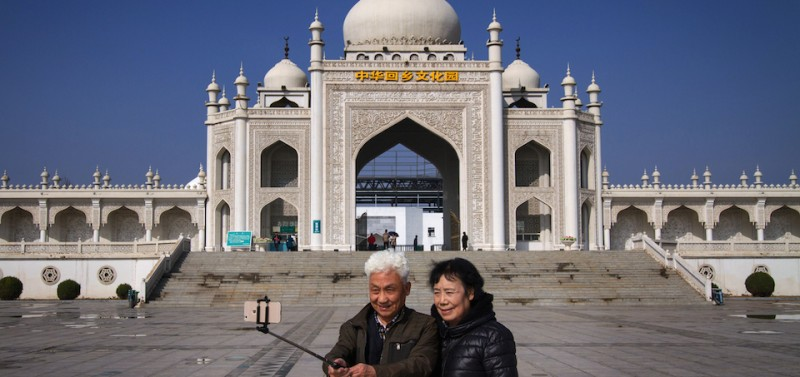 Visitors take a selfie photo in front of a Taj Mahal replica that serves as the gate to the Hui Culture Park.