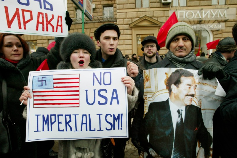 MOSCOW - JANUARY 18:  Demonstrators with a picture of Iraqi leader Saddam Hussein shout anti-U.S. slogans during a rally outside the U.S. Embassy against the possible war with Iraq January 18, 2003 in Moscow. The protest, organized by the Moscow branch of the Russian Communist Party, was joined by Iraqis and citizens of other Arab countries. (Photo by Oleg Nikishin/Getty Images)