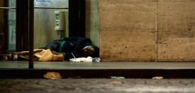 A homless person sleeps outside the Termini train station on November 18, 2014 in Rome. AFP PHOTO / TIZIANA FABI        (Photo credit should read TIZIANA FABI/AFP/Getty Images)