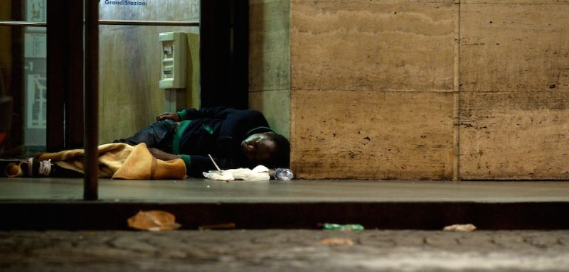 A homless person sleeps outside the Termini train station on November 18, 2014 in Rome. AFP PHOTO / TIZIANA FABI        (Photo credit should read TIZIANA FABI/AFP/Getty Images)