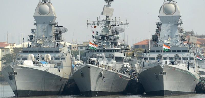 Indian naval sailors on a rubber inflatable boat pass naval warships at the Naval Dockyard in Mumbai on April 20, 2015.  AFP PHOTO/ Indranil MUKHERJEE        (Photo credit should read INDRANIL MUKHERJEE/AFP/Getty Images)