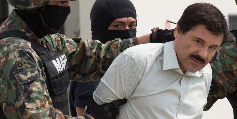 The drug trafficker Joaquin Guzman Loera, El Chapo, looks at the press, guarded by members of Mexican Navy is moved to a helicopter. El chapo, was arrested Saturday at 6:40 hours at a hotel in Mazatlan, Sinaloa in Mexico city, Mexico, on Saturday, Feb. 22, 2014. Photographer: Susana Gonzalez/Bloomberg