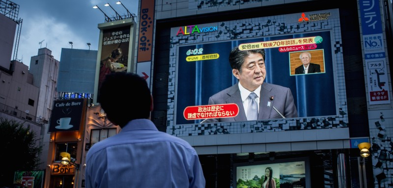 "TOKYO, JAPAN - AUGUST 14:  A man watches a big screen showing a live broadcast of Japanese Prime Minister, Shinzo Abe as he delivers his WWII Anniversary Statement on August 14, 2015 in Tokyo, Japan. Japanese Prime Minister Abe delivered a war anniversary statement ahead of the anniversary of Japan's defeat in the second world war. The statement included such keywords as ""apology from the heart,"" ""colonial rule,"" and ""aggression.""  (Photo by )"