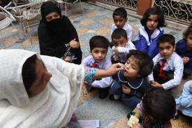 A Pakistani health worker administers polio drops to a child at a school during a polio vaccination campaign in Peshawar on September 14, 2015. Pakistan is one of only three countries in the world where polio remains endemic but years of efforts to stamp it out have been badly hit by reluctance from parents, opposition from militants and attacks on immunisation teams. AFP PHOTO / A MAJEED        (Photo credit should read A Majeed/AFP/Getty Images)