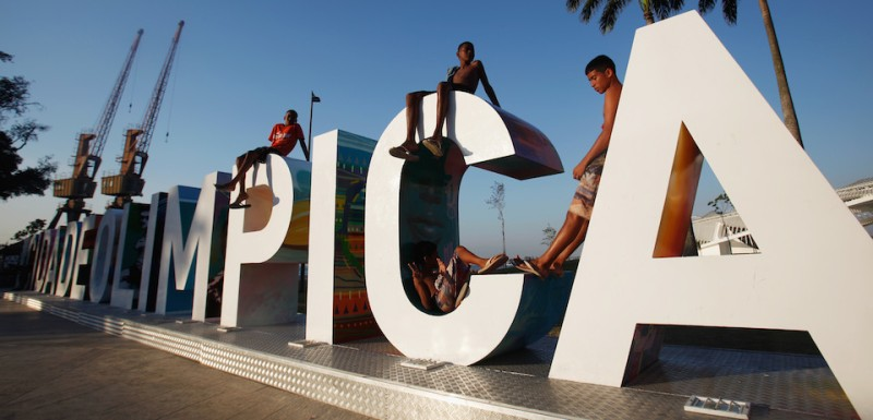 RIO DE JANEIRO, BRAZIL - OCTOBER 15:  Teens sit on a new sign reading 'Cidade Olimpica' (Olympic City) in the historic port district on October 15, 2015 in Rio de Janeiro, Brazil. Ahead of the Rio 2016 Olympic Games games, the port district is undergoing a controversial multibillion dollar urban renewal program although some projects have been delayed in the midst of Brazil's recession. Many parts of the port district retain descendants of African slaves along with Afro-Brazilian historical locations including the area where samba music is thought to have been born in Rio.  (Photo by Mario Tama/Getty Images)