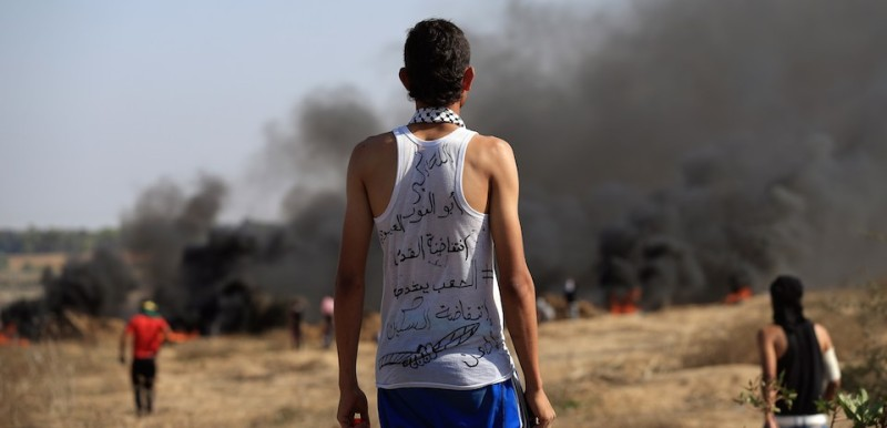 "A Palestinian protester wearing a shirt with Arabic writting on it looks on as smoke billows during clashes with Israeli soldiers near the border fence between Israel and the central Gaza Strip east of Bureij on October 16, 2015. Palestinians called for a ""Friday of revolution"" against Israel, as Jews armed themselves with everything from guns to broomsticks, rattled by a wave of Palestinian attacks that have shaken the country. Arabic writting on shirt reads ""Al-Quds Intifada and Knife Intifada."" AFP PHOTO / MOHAMMED ABED        (Photo credit should read MOHAMMED ABED/AFP/Getty Images)"