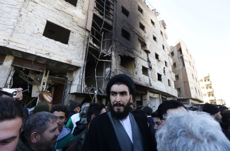 A Shiite cleric stands amid Syrian pro-government forces and residents at the site of suicide bombings in the area of a revered Shiite shrine in the town of Sayyida Zeinab, on the outskirts of the capital Damascus, on January 31, 2016. The Islamic State group claimed responsibility for the bombings that killed at least 45 people. / AFP / LOUAI BESHARA        (Photo credit should read LOUAI BESHARA/AFP/Getty Images)