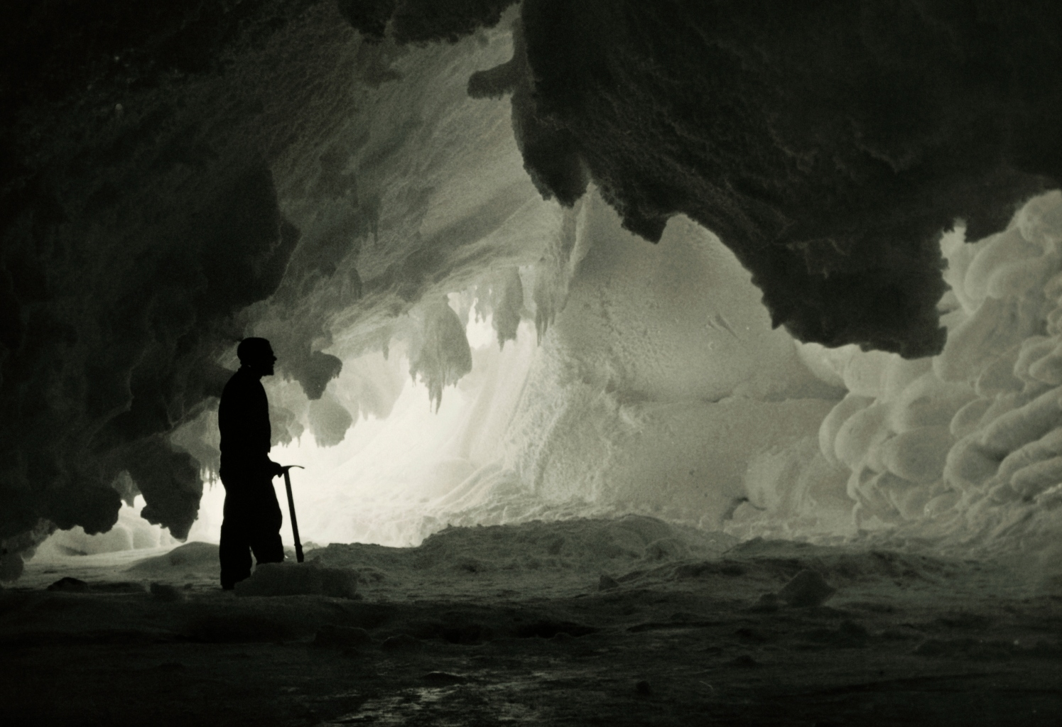 (Original Caption) Antarctica: Interior of ice cave about 10 miles from McMurdo Station. A man with an icepick stands there. Undated photograph.