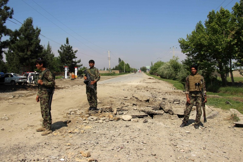 Afghan security personnel stand near the crater of a bomb after fighting against Taliban militants at Charkhab in Kunduz province on April 23, 2016.  Afghan security forces drove Taliban fighters back from Kunduz city, officials said, as the insurgents began the 2016 fighting season by targeting the northeastern provincial capital they briefly captured last year. / AFP / NASIR WAQIF        (Photo credit should read NASIR WAQIF/AFP/Getty Images)