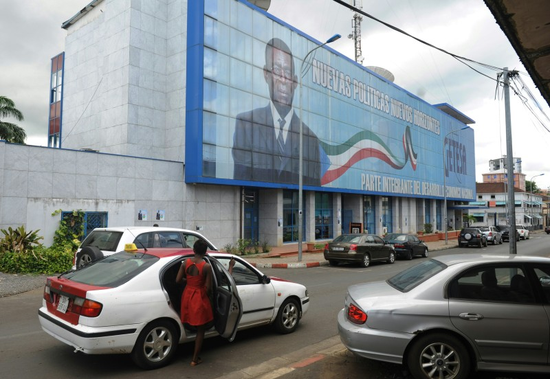 Residents walk by a large electoral banner of Equatorial Guinea incumbent president and candidate Teodoro Obiang in Malabo on April 23, 2016.  Africa's longest-serving ruler, Equatorial Guinea President incumbent President and Presidential candidate Teodoro Obiang Nguema Mbasogo, looks set to win a fresh seven-year term that could also see him nail the all-time record for African leaders, living or dead. / AFP / STRINGER        (Photo credit should read STRINGER/AFP/Getty Images)