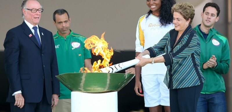 BRASILIA, BRAZIL - MAY 03:  Dilma Rousseff, President of Brazil, lights the Olympic torch with Brazilian Olympic Committee Carlos Nuzman (L) and first torch bearer, volleyball player Fabiana Claudino at the Palacio do Planalto on May 3, 2016 in Brasilia, Brazil. The Olympic torch will pass through 329 cities from all states from the north to the south of Brazil, until arriving in Rio de Janeiro on August 5, to lit the cauldron.  (Photo by Buda Mendes/Getty Images)