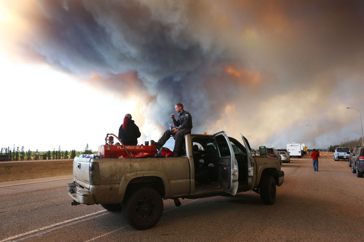 A group trying to rescue animals from Fort McMurray wait at road block on Highway 63 near as smoke rises from a forest fire near Fort McMurray, Alberta on May 6, 2016. Canadian police led convoys of cars through the burning ghost town of Fort McMurray Friday in a risky operation to get people to safety far to the south.In the latest chapter of the drama triggered by monster fires in Alberta's oil sands region, the convoys of 50 cars at a time are driving through the city at about 50-60 kilometers per hour (30-40 miles per hour) TV footage showed. / AFP / Cole Burston/ (Photo credit should read COLE BURSTON//AFP/Getty Images)
