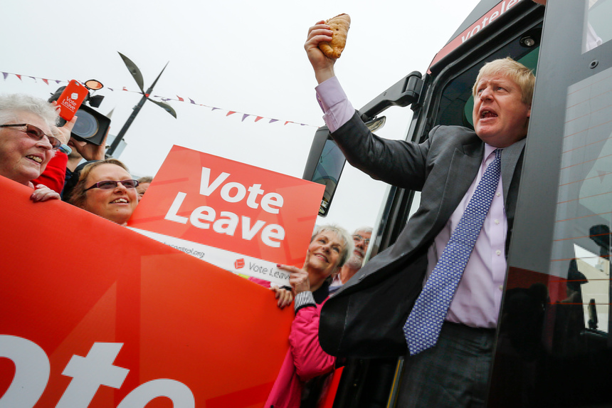 "Boris Johnson, the former mayor of London, waves a Cornish Pasty during the first day of a nationwide bus tour to campaign for a so-called Brexit in Truro, U.K., on Wednesday, May 11, 2016. While online polls suggest the contest for the June 23 referendum is too close to call, less frequent telephone polling has put the ""Remain"" camp ahead. Photographer: Luke MacGregor/Bloomberg via Getty Images"