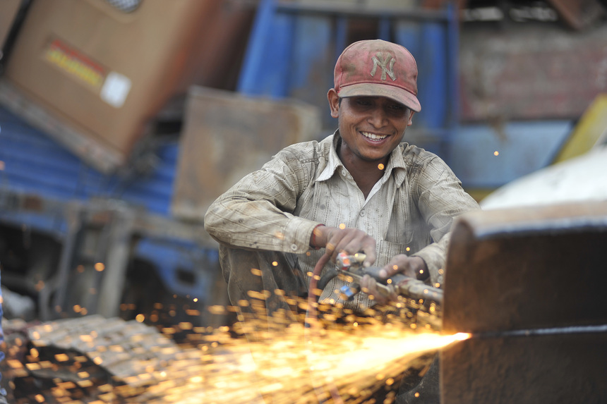 SUDHIR KUMAR PATEL, 28 yrs old, migrated from India smiles as Cutting heavy duty roller's Metal with Oxygen Acetylene Gas as Spark splash around the ground at Kathmandu, Nepal on May 11, 2016. Patel use to earn daily wage of NRs. 700 (US$ 7). (Photo by Narayan Maharjan/NurPhoto via Getty Images)