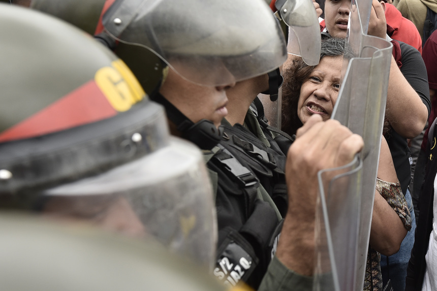 A protester yells at Venezuelan National Guard members during an opposition march in Caracas, Venezuela, on Wednesday, May 11, 2016. About 8,000 opposition supporters attempted to march to the downtown office of the national electoral board (CNE) in Caracas today to demand that the agency comply with specified time frame to verify signatures collected in first phase of process to call for recall referendum on President Nicolas Maduro. Photographer: Carlos Becerra/Bloomberg via Getty Images