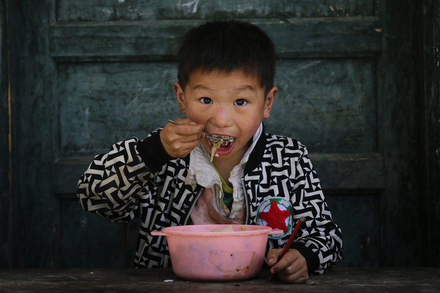 "UNSPECIFIED, CHINA - MAY 10:  A student eats a free lunch at school on May 10, 2016 in Miao Autonomous Country of Songtao,Guizhou Province, China. Long Huofa is the principal of Bajiao village primary school. There are 136 students and seven teachers in the school. Bajiao village is located in Miao Autonomous Country of Songtao, Guizhou Province, China. Surrounded by mountains, the village is very poor. Most young villagers go out to work, leaving the elderly and children in home. Long Huofa became the teacher of Bajiao village school in 1988, served as principal in 2007. Unfortunately, he sufferd from nasal carcinoma in 2011. But he insisted to return the job after brief treatment. Due to the radiotherapy and chemotherapy, his hair turned white, so his students always called him ""silver principal"" affectionately. (Photo by Wang HE/Getty Images)"