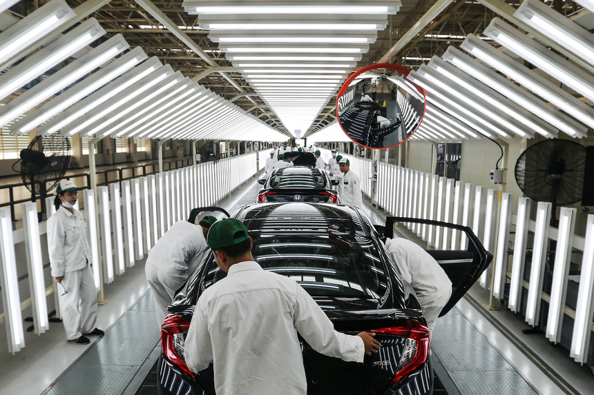 Employees check Honda Civic vehicles at the quality control station on the production line of the Honda Motor Co. assembly plant in Prachinburi, Prachinburi Province, Thailand, on Thursday, May 12, 2016. The new facility will have a maximum production capacity of 120,000 vehicles per year. Photographer: Dario Pignatelli/Bloomberg via Getty Images