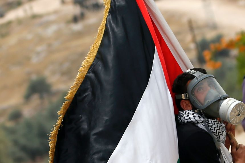 A Palestinian protester, wearing a gas mask, holds a Palestinian flag on May 13, 2016 in the West Bank village of Bilin, near Ramallah, during a march against the building of Israel's controversial separation barrier and the construction of Israel settlement. / AFP / ABBAS MOMANI        (Photo credit should read ABBAS MOMANI/AFP/Getty Images)