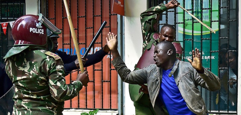 Kenyan riot police officers hold batons as they detain a suspected supporter of the Kenya's opposition Coalition for Reforms and Democracy (CORD), during a protest on May 16, 2016 in Nairobi, outside the headquarters of the Independent Electoral and Boundaries Commission (IEBC). Opposition protestors led by former Prime Minister Raila Odinga gathered outside the Indepedent Electoral and Boundaries Comission building to demand the dismissal of IEBC commissioners, after alleged bias towards the ruling Jubillee Alliance Party. / AFP / CARL DE SOUZA        (Photo credit should read CARL DE SOUZA/AFP/Getty Images)