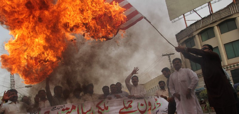 "A Pakistani demonstrator holds a burning US flag as others shout slogans during a protest  in Multan on May 24, 2016, against a US drone strike in Pakistan's southwestern province Balochistan.   Slain Afghan Taliban leader Mullah Akhtar Mansour used a Pakistani passport in a false name to make dozens of foreign trips over a ten-year period, mainly to the United Arab Emirates, officials told AFP. Mansour, who was killed in a US drone strike deep inside Pakistani territory on May 21 along with a driver, was travelling with a passport and ID card bearing the name ""Muhammad Wali"". / AFP / SS MIRZA        (Photo credit should read SS MIRZA/AFP/Getty Images)"