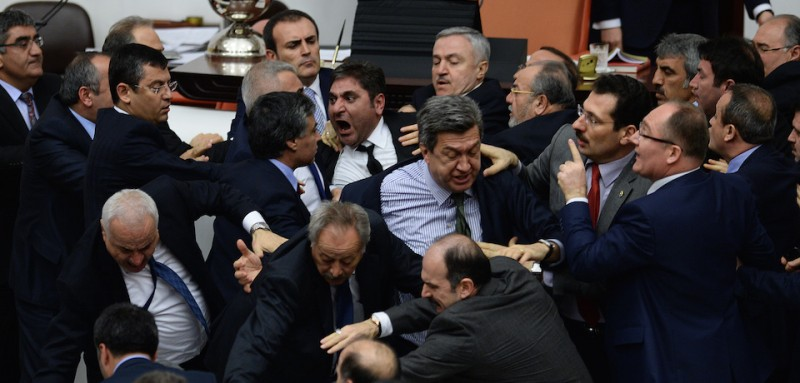 epa04628494 A picture made avaliable on 20 February 2015 of members of Turkey's ruling party Justice and Development Party (AKP) and members of opposition parties throwing punches at each other during a debate at the Turkish Parliament in Ankara, Turkey, late 19 February 2015. At least five members of the parliament were injured in the scuffles during the parliament session about an Internal Security resolution in last two days, according to local media reports.  EPA/STR