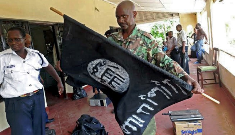 A Kenyan police officer folds up a flag inscribed with the logo of the Islamic state (IS) following a raid on two mosques in the coastal city of Mombasa, on November 17, 2014.  One man was killed  as Kenyan security forces arrested over 200 people and seized weapons in raids on mosques accused of links with Somalia's Al-Qaeda affiliated Shebab militants, police said. Security forces began the operation in the early hours of Monday morning, targeting the Masjid Musa and Sakina mosques in the port city of Mombasa. AFP PHOTO/STR        (Photo credit should read STRINGER/AFP/Getty Images)