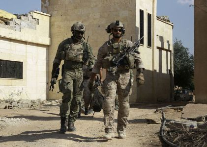 Armed men in uniform identified by Syrian Democratic forces as US special operations forces walk in the village of Fatisah in the northern Syrian province of Raqa on May 25, 2016. US-backed Syrian fighters and Iraqi forces pressed twin assaults against the Islamic State group, in two of the most important ground offensives yet against the jihadists. The Syrian Democratic Forces (SDF), formed in October 2015, announced on May 24 its push for IS territory north of Raqa city, which is around 90 kilometres (55 miles) south of the Syrian-Turkish border and home to an estimated 300,000 people. The SDF is dominated by the Kurdish People's Protection Units (YPG) -- largely considered the most effective independent anti-IS force on the ground in Syria -- but it also includes Arab Muslim and Christian fighters. / AFP / DELIL SOULEIMAN (Photo credit should read DELIL SOULEIMAN/AFP/Getty Images)