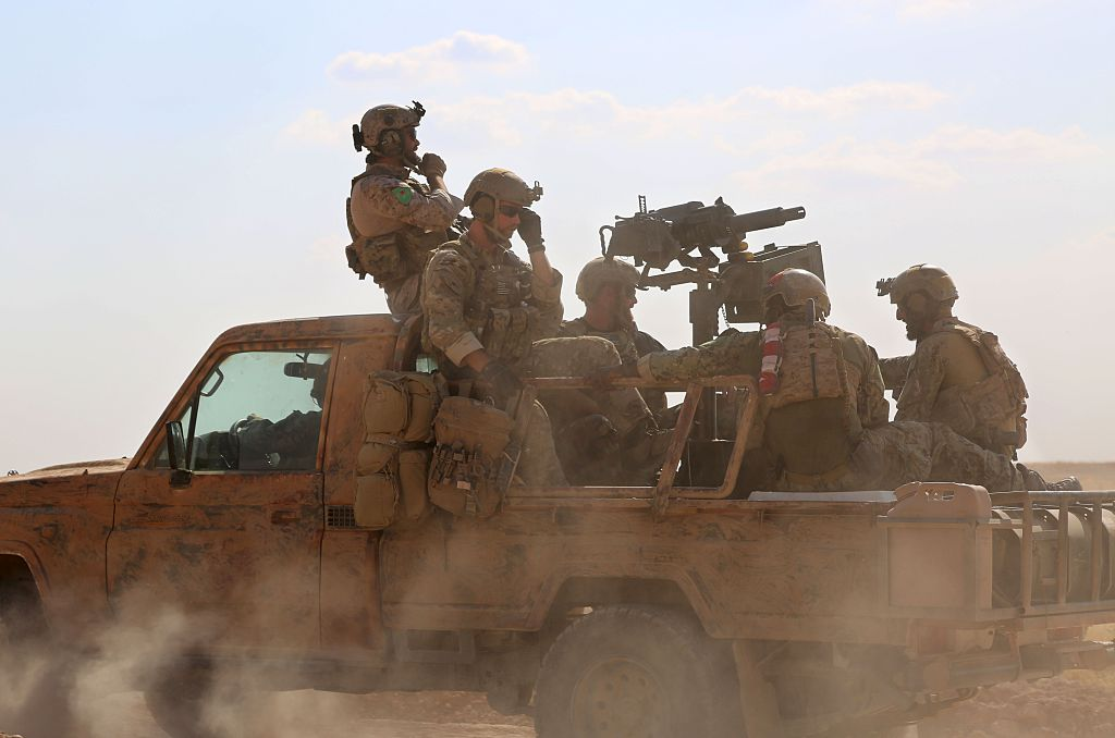 TOPSHOT - Armed men in uniform identified by Syrian Democratic forces as US special operations forces ride in the back of a pickup truck in the village of Fatisah in the northern Syrian province of Raqa on May 25, 2016. US-backed Syrian fighters and Iraqi forces pressed twin assaults against the Islamic State group, in two of the most important ground offensives yet against the jihadists. The Syrian Democratic Forces (SDF), formed in October 2015, announced on May 24 its push for IS territory north of Raqa city, which is around 90 kilometres (55 miles) south of the Syrian-Turkish border and home to an estimated 300,000 people. The SDF is dominated by the Kurdish People's Protection Units (YPG) -- largely considered the most effective independent anti-IS force on the ground in Syria -- but it also includes Arab Muslim and Christian fighters. / AFP / DELIL SOULEIMAN (Photo credit should read DELIL SOULEIMAN/AFP/Getty Images)
