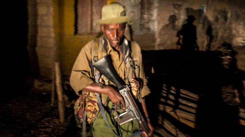 A home guard walks through a Mandera suburb late at night. Many homeguards chew the local stimulant khat to stay alert.