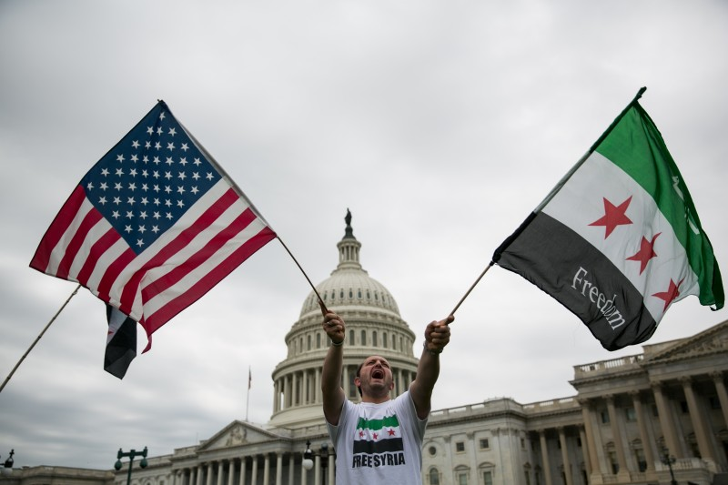 WASHINGTON, DC - SEPTEMBER 9:  Jehad Sibai waves flags during a rally in support of possible U.S. military action in Syria, on Capitol Hill, on September 9, 2013 in Washington, DC. U.S. President Barack Obama will address the American people on Syria from the White House on Tuesday.  (Photo by Drew Angerer/Getty Images)