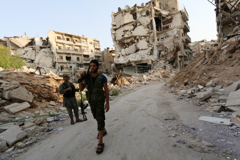 Rebel fighters walk in front of damaged buildings in Karm al-Jabal neighbourhood of Aleppo on August 26, 2014. The United States has begun reconnaissance flights over Syria and is sharing intelligence about jihadist deployments with Damascus through Iraqi and Russian channels, sources told AFP.   AFP PHOTO/AMC/ZEIN AL-RIFAI        (Photo credit should read ZEIN AL-RIFAI/AFP/Getty Images)