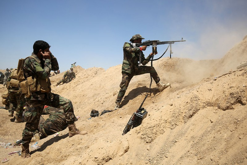 Iraqi government forces fire their weapons near al-Sejar village, north-east of Fallujah, on May 26, 2016, as they take part in a major assault to retake the city from the Islamic State (IS) group. Tens of thousands of security forces are deployed in the Fallujah area for an assault aimed at retaking the city from the Islamic State group. Fallujah, which lies only 50 kilometres (30 miles) west of Baghdad, has been out of government control since January 2014 and is one of only two remaining major Iraqi cities still in IS hands, the other being Mosul. / AFP / AHMAD AL-RUBAYE        (Photo credit should read AHMAD AL-RUBAYE/AFP/Getty Images)