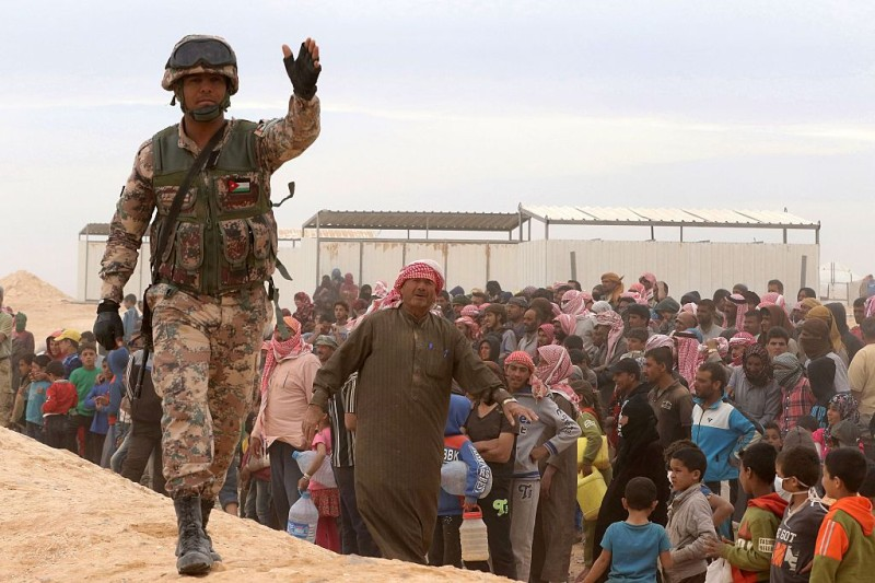 A Jordanian soldier stands guard as Syrian refugees arrive to a camp on the Jordanian side at the north east of Jordan's border with Syria, at the Al-Hadalat crossing point in the eastern town of Ruwaished, on May 4, 2016. According to the Jordanian Commander of the Border Guards Brigadier Saber Al-Mahayreh, around 5000 Syrians fleeing from recent attacks on the northern Syrian city of Aleppo are trying to cross into Jordan in search of safety and most are exhausted and desperately in need of help and medical treatment. / AFP / KHALIL MAZRAAWI        (Photo credit should read KHALIL MAZRAAWI/AFP/Getty Images)