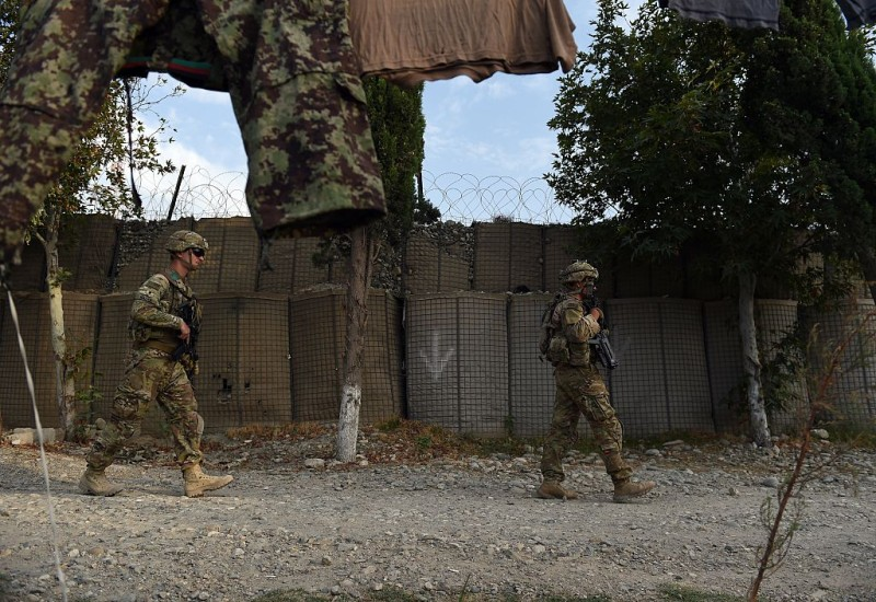 "TO GO WITH AFGHANISTAN-US-ARMY-CONFLICT-FOCUS BY GUILLAUME DECAMME  In this photograph taken on August 12, 2015, US army soldiers walk past an Afghan National Army (ANA) base in the Khogyani district in the eastern province of Nangarhar. From his watchtower in insurgency-wracked eastern Afghanistan, US army Specialist Josh Whitten doesn't have much to say about his Afghan colleagues. ""They don't come up here anymore, because they used to mess around with our stuff. ""Welcome to Forward Operating Base Connelly, where US troops are providing training and tactical advice to the 201st Afghan army corps as they take on the Taliban on the battlefield. AFP PHOTO / Wakil Kohsar        (Photo credit should read WAKIL KOHSAR/AFP/Getty Images)"