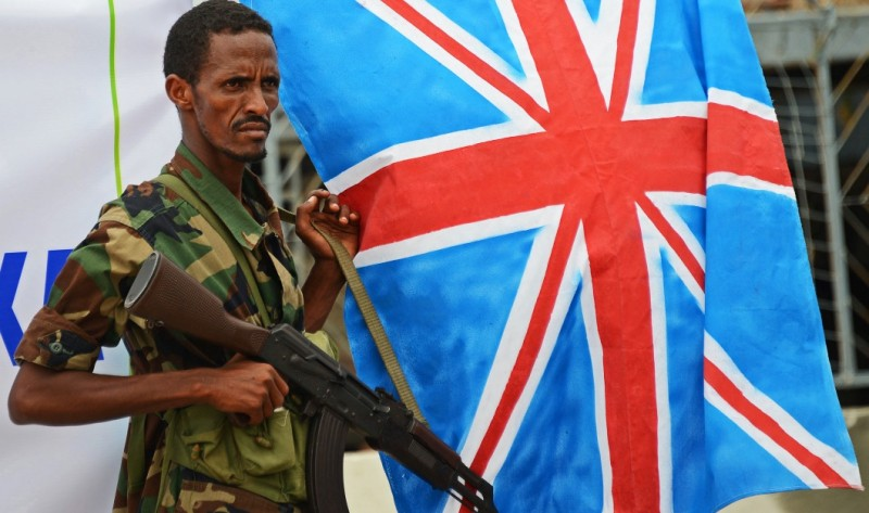 A Somali Transitional Federal Government  (TFG) soldier stands next to the Union Jack flag in Mogadishu, on May 7, 2013. Hundreds of Somalis marched through the capital to support a London conference attended by more than 50 countries and organisations, co-hosted by Britain Prime Minister David Cameron and Somali President Hassan Sheikh Mohamud. The conference is a diplomatic meeting by leaders and organisations to coordinate efforts to help Somalia rebuild, following two decades of civil war. AFP PHOTO/Mohamed Abdiwahab        (Photo credit should read Mohamed Abdiwahab/AFP/Getty Images)