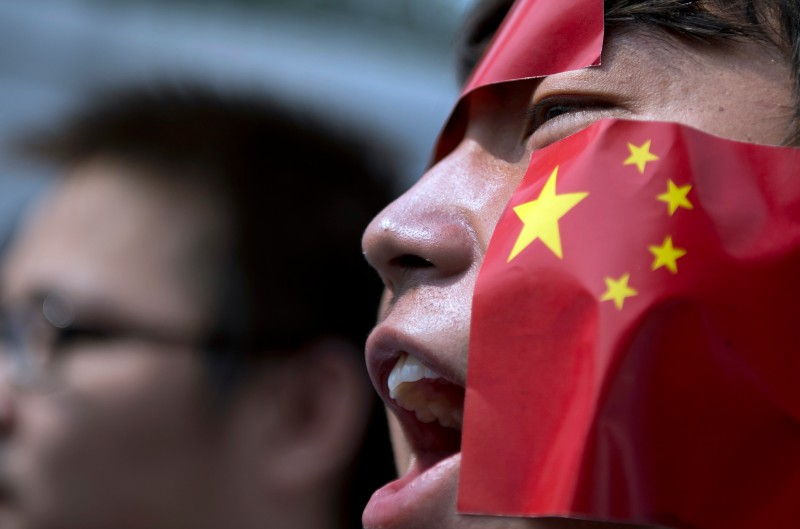 "A Chinese national living in Malaysia shouts wears stickers of the Chinese national flag on his face as he shouts slogans during a protest against Japan's ""nationalizing"" of disputed islands known as Diaoyu in Chinese and as Senkaku in Japan, in front of the Japanese embassy in Kuala Lumpur on September 19, 2012. The islands are controlled by Japan but claimed by China and Taiwan, and the current row has roiled the political relationship between Beijing and Tokyo, which is coloured by Chinese resentment over past conflicts and atrocities.  AFP PHOTO / Saeed Khan        (Photo credit should read SAEED KHAN/AFP/GettyImages)"