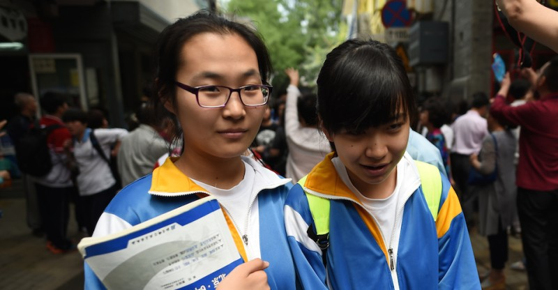 "Two students walk out together after sitting a university entrance exam in Beijing on June 7, 2016.  Millions of children across China began sitting the annual two-day  ""gaokao"" university entrance exams on June 7. The exams are a national obsession which decides the fates of millions. / AFP / GREG BAKER        (Photo credit should read GREG BAKER/AFP/Getty Images)"