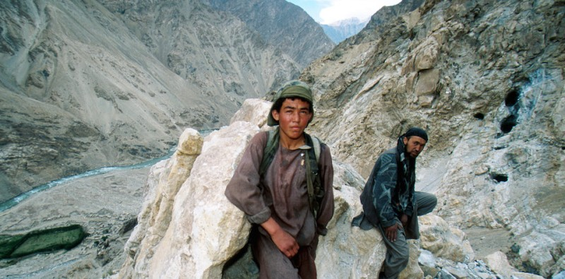 392910 17: (NEWSWEEK, US NEWS & WORLD REPORT OUT) A water boy, center, rests on a ridge May 2001 while carrying water to the Sar-e-sang lapis lazuli mine in the Hindu Kush mountain range above Madan, Afghanistan. Afghani opposition leader Ahmed Shah Massoud, who controls the region, is using a tax on gems mined and sold in the valley to buy armaments to continue his guerrilla war with the ruling Taliban. (Photo by Robert Nickelsberg/Getty Images)
