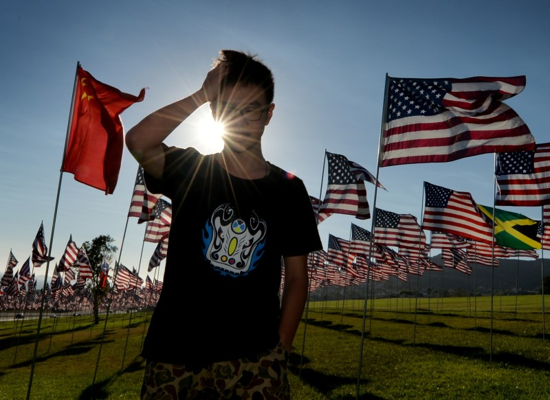 Chinese exchange student Jason Chai next to a Chinese flag that sits amongst US national flags erected by students and staff from Pepperdine University who placed nearly 3000 flags in the ground to honor each victim of the September 11, 2001 attacks in Malibu on September 9, 2014.          AFP PHOTO/Mark RALSTON        (Photo credit should read MARK RALSTON/AFP/Getty Images)