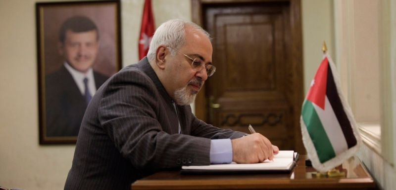 Iranian Foreign Minister Mohammad Javad Zarif signs the visitor's book follwoing his meeting with his Jordanian counterpart Nasser Judeh (unseen) on January 14, 2014 in Amman. Over the past two days Zarif has visited Lebanon and Iraq as part of a regional tour. AFP PHOTO/POOL/MOHAMMAD HANNON        (Photo credit should read )