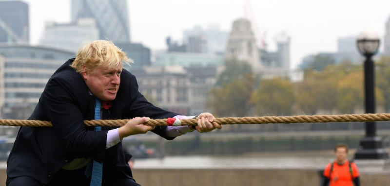 "LONDON, ENGLAND - OCTOBER 27:  Mayor of London Boris Johnson competes in a tug of war during the launch of London Poppy Day on October 27, 2015 in London, England. Poppies have been used to commemorate soldiers who have died in conflict since 1914 and are distributed by the British Royal Legion in the UK in return for donactions to the ""Poppy Appeal"".  (Photo by Ben Pruchnie/Getty Images)"