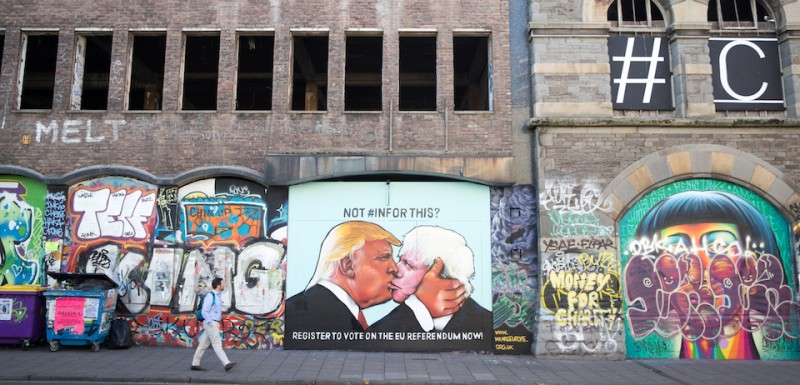 BRISTOL, UNITED KINGDOM - MAY 24:  A man passes a mural that has been painted on a derelict building in Stokes Croft showing US presidential hopeful Donald Trump sharing a kiss with former London Mayor Boris Johnson on May 24, 2016 in Bristol, England. Boris Johnson is currently one of the biggest names leading the campaign for Britain to leave the European Union in the referendum which takes place on June 23 and Republican presidential hopeful Donald Trump has also backed a so-called Brexit.  (Photo by )