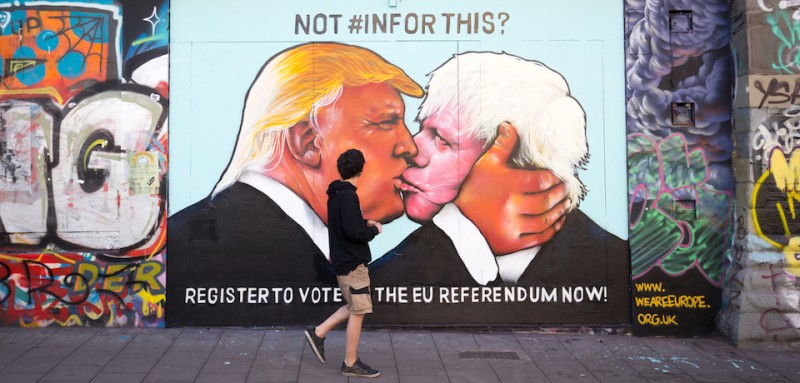 BRISTOL, UNITED KINGDOM - MAY 24:  A man passes a mural that has been painted on a derelict building in Stokes Croft showing US presidential hopeful Donald Trump sharing a kiss with former London Mayor Boris Johnson on May 24, 2016 in Bristol, England. Boris Johnson is currently one of the biggest names leading the campaign for Britain to leave the European Union in the referendum which takes place on June 23 and Republican presidential hopeful Donald Trump has also backed a so-called Brexit.  (Photo by Matt Cardy/Getty Images)